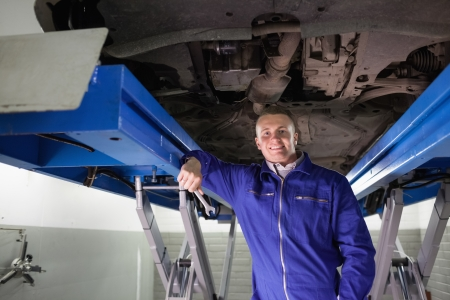 Smiling mechanic leaning on a machine in a garage Stock Photo - 16208916