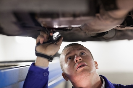 Mechanic illuminating the car with a flashlight in a garage Stock Photo - 16208503