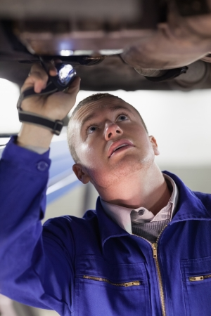 Mechanic illuminating the below of a car with a flashlight in a garage Stock Photo - 16208945