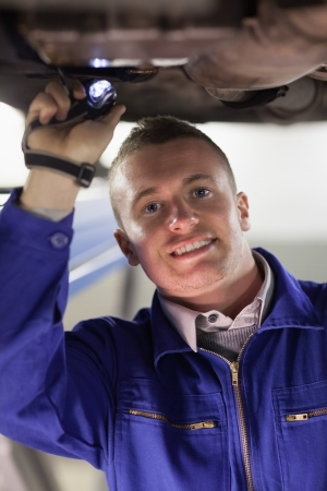 gudgeon: Mechanic illuminating the below of a car in a garage Stock Photo