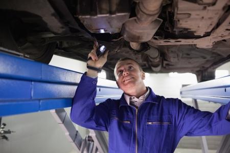 garage automobile: Sourire mécanicien éclairer une voiture avec une lampe de poche dans un garage
