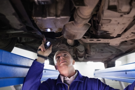 Concentrated mechanic illuminating a car with a flashlight in a garage Stock Photo - 16208918