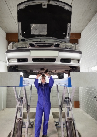 gudgeon: Mechanic standing while repairing a car in a garage