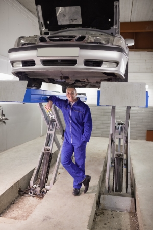 gudgeon: Smiling man leaning on a machine in a garage