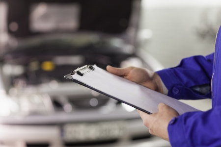 Close up of a man holding a clipboard in a garage photo