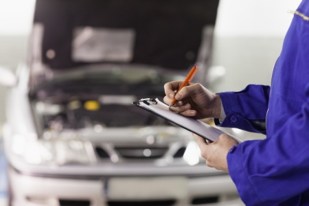 car repair: Close up of a man writing on a clipboard in a garage