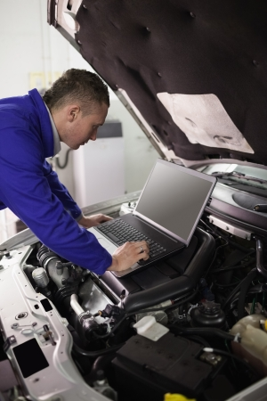 mechanician: Mechanic looking at a computer on a car engine in a garage Stock Photo