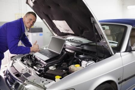 car engine: Mechanic leaning on a car engine in a garage