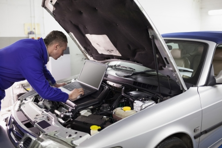 mechanician: Mechanic typing on a computer while looking it in a garage