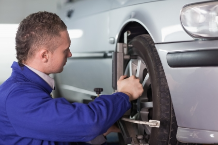 service car: Concentrated mechanic repairing a car wheel in a garage Stock Photo