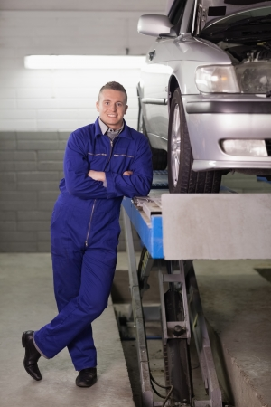 gudgeon: Front view of a mechanic with arms crossed in a garage