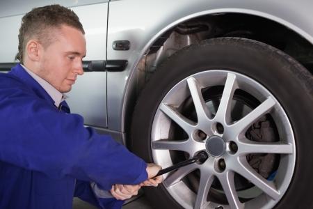 gudgeon: Man repairing a car wheel in a garage