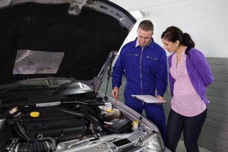 garage automobile: M�canicien montrant un pied d'�galit� du moteur � une femme dans un garage