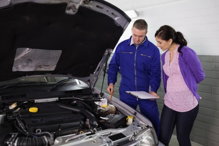 par: Mechanic showing a par of the engine to a woman in a garage