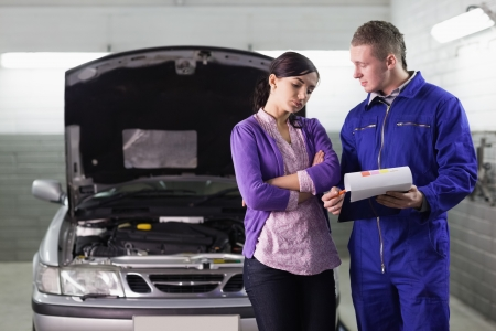 mechanician: Mechanic showing the quotation to a client in a garage Stock Photo