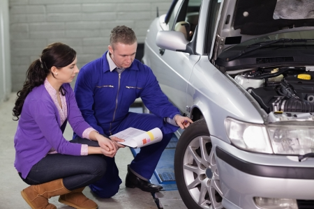 car repair: Mechanic showing the car wheel to a client in a garage