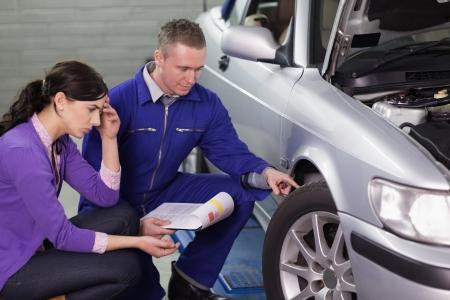 garage automobile: Mécanicien regardant la roue de la voiture à côté d'un client dans un garage