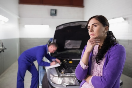 gudgeon: Thoughtful woman next to a car in a garage Stock Photo