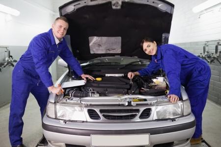 garage automobile: M�canique s'appuyant sur une voiture dans un garage
