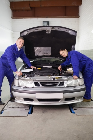 gudgeon: Mechanics smiling while leaning on a car in a garage Stock Photo