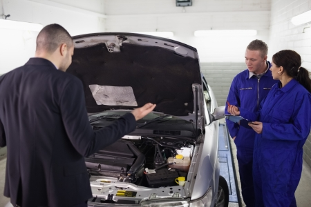 gudgeon: Client looking at a car next to mechanics in a garage