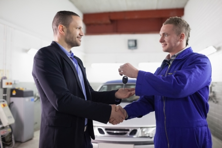operating key: Man receiving car key while shaking hand to a mechanic in a garage