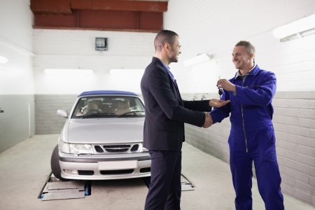 Mechanic giving car key while shaking hand to a client in a garage photo