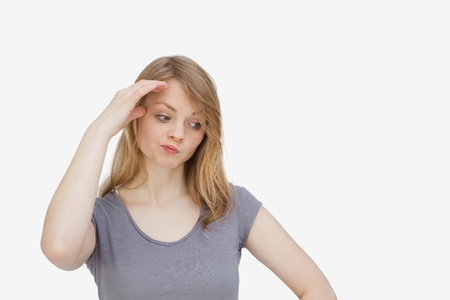 lost in thought: Woman being lost in thought against a white background Stock Photo