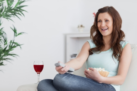 Woman smiling while pressing a remote control in a living room photo