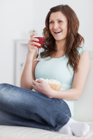 Woman holding a glass of wine and a bowl of popcorn in a living room photo