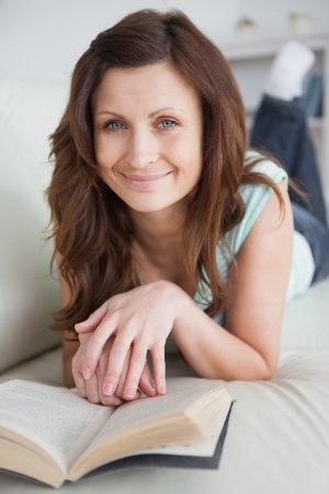Woman lying on the belly on a sofa looking at camera in a living room photo