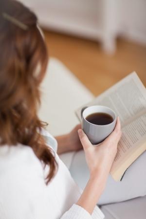 Hög bild av en kvinna med en kopp kaffe i ett vardagsrum