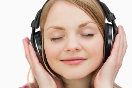 ojos cerrados: Primer plano de una mujer con los auriculares contra un fondo blanco Foto de archivo