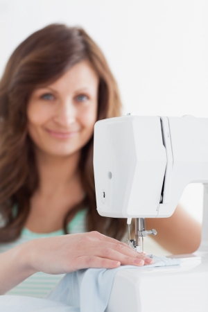 Woman using a sewing machine against a white background Stock Photo - 16203576
