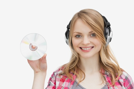 mirthful: Woman holding a cd while wearing headphones against a white abckground