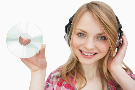 Woman smiling while holding a cd against a white background