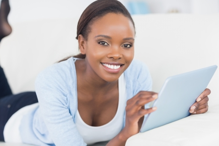 Black woman smiling while holding a tablet computer in a living room photo