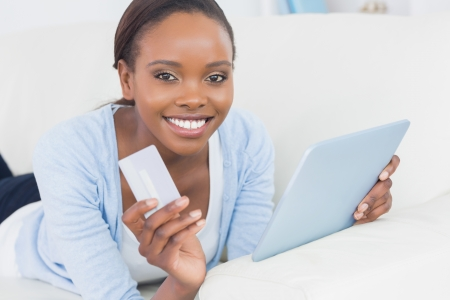 credit card reader: Black woman holding a tablet computer and a credit card in a living room