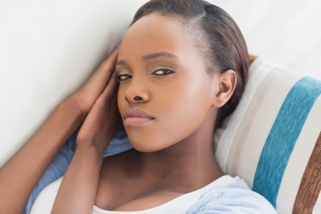 solicitous: Black woman looking at camera while lying in a living room