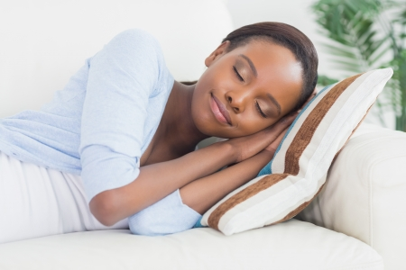 calm woman: Black woman sleeping while lying on side in a living room