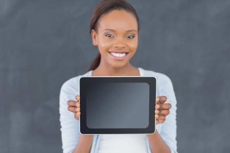 Black woman holding a tablet computer next to a blackboard in a classroom photo