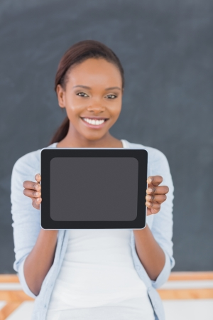 Smiling black woman holding a tablet computer in a classroom photo