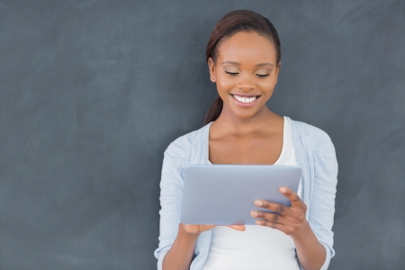 woman tablet: Front view of a black woman holding a tablet computer in a classroom
