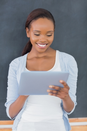 Front view of a black woman looking at a tablet computer in a classroom photo