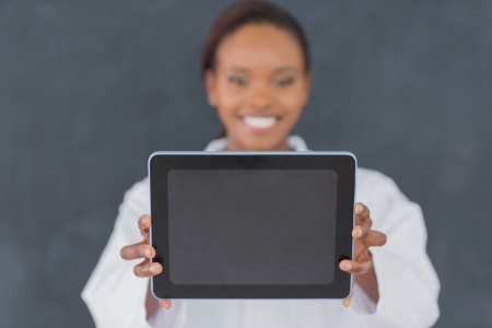 Focus on a black woman holding an ebook in a classroom photo