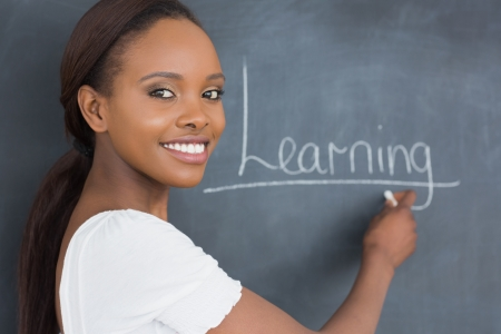 Teacher showing the blackboard while smiling in a classroom Stock Photo - 16207915