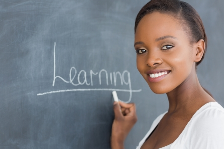 adult learning: Black woman smiling while looking at camera in a classroom
