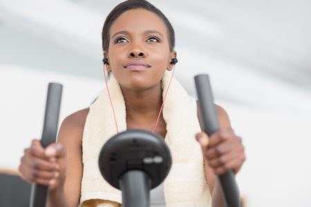Low angle view of a black woman doing exercise bike in a living room photo