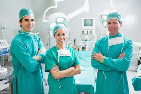Surgeons standing up with arms crossed in an operating theatre photo