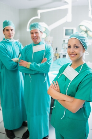 Surgical team standing up with arms crossed in an operating theatre photo